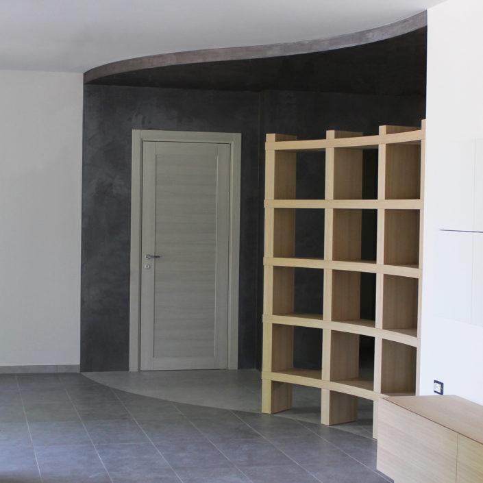 Libreria in legno curvato, segue il disegno del pavimento e divide l'ingresso dal living.